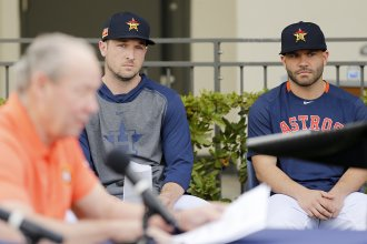 Houston Astros players Alex Bregman and José Altuve look on as owner Jim Crane addresses reporters during a news conference Thursday in West Palm Beach, Fla.