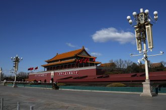 A masked paramilitary policeman stands guard alone at a deserted Tiananmen Gate in Beijing following the coronavirus outbreak. China on Wednesday said it has revoked the press credentials of three U.S. reporters over a headline for an opinion column it deems racist and slanderous.