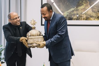 Ethiopian Prime Minister Abiy Ahmed (right) receives the crown from the man who found it, Sirak Asfaw, during a ceremony Thursday in Addis Ababa. The 18th-century Ethiopian crown had been hidden in a Dutch apartment for the past 21 years.