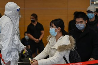 Airport security staff wearing protective gear check passengers arriving at Shanghai Pudong International Airport on March 19, the day China reported no new domestic cases of the coronavirus for the first time since it started recording them in January.