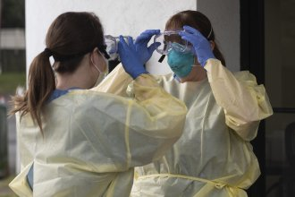 Health care workers from Virginia Hospital Center put on their personal protective equipment before people arrive at a drive-through coronavirus testing site in Arlington, Va., on Friday.