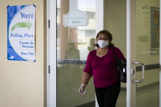 A woman wearing mask and protective gloves leaves after cast her vote during the Florida Democratic primary election in Miami, Florida, on March 17, 2020. The latest Senate coronavirus relief bill includes $400 million to states to ensure upcoming elections are safe for voters and pollworkers.