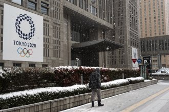 The International Olympic Committee has set firm dates for the delayed Tokyo 2020 Olympics, which will now start in July of 2021. Here, a man walks past a banner promoting the Tokyo 2020 Olympics Sunday, after a late-season snow in Tokyo. Millions of Tokyo residents were asked to stay home this weekend, due to the new coronavirus.