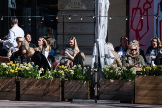 People enjoy the spring weather as they sit at a restaurant in Stockholm on April 15 during the coronavirus pandemic.
