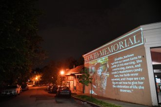 "Video artist Robin Bell projected the words ""Covid Memorial,"" onto the brick wall of a Subway sandwich shop in Washington, D.C. Below them scrolled a slideshow of faces of COVID-19 victims, along with messages their loved ones had posted on social media."