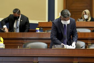 Rep. Tony Cardenas, D-Calif., cleans his desk during a House Energy and Commerce Subcommittee on Health hearing earlier this month.