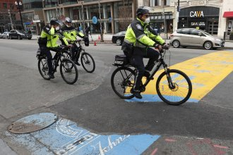 Boston police officers ride past the finish line of the Boston Marathon, which was canceled and replaced with a virtual event on Thursday.