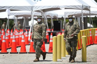 Members of the Florida National Guard are seen at a coronavirus testing site on April 27 in North Miami. Restrictions are easing, but officials worry people might now hesitate to evacuate during a hurricane.