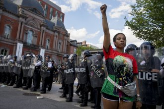 A woman stands in front of a line of police officers near the White House during a protest in Washington, D.C.
