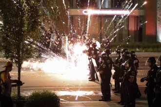 A firework explodes by a police line as demonstrators gather to protest the death of George Floyd on Saturday near the White House in Washington.