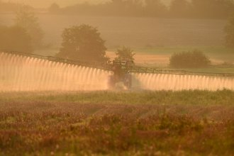 Bayer says a settlement worth more than $10 billion will resolve most of the roughly 125,000 claims the company currently faces over its Roundup product. Here, a farmer sprays the glyphosate herbicide in northwestern France in September.