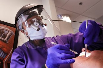 Dental offices have begun seeing patients return for routine procedures. Seattle dentist Kathleen Saturay has increased the layers of protective equipment she wears when treating patients.