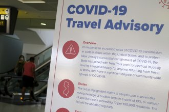 A sign at Newark Liberty International Airport warns airline passengers about a travel advisory that applies to people arriving in New Jersey from certain states. Visitors from Alabama, Arkansas, Arizona, California, Florida, Georgia, Iowa, Idaho, Louisiana, Mississippi, Nevada, North Carolina, South Carolina, Tennessee, Texas and Utah should self-quarantine for two weeks.