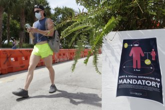 A pedestrian in a mask passes a sign urging people to practice social distancing, on Saturday in Miami Beach, Fla. Just as residents flocked outside to enjoy the Fourth of July, states such as Florida were reporting skyrocketing numbers of confirmed coronavirus cases.