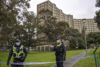 Police guard access to housing commission apartments under lockdown in Melbourne, Australia. The hard-hit Australian state of Victoria recorded two deaths and its highest-ever daily increase in coronavirus cases on Monday as authorities prepare to close its border with New South Wales.