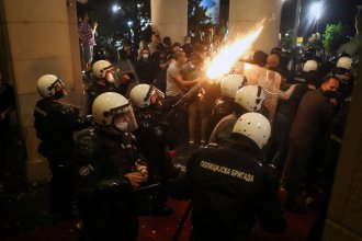Protesters clash with police Tuesday night in front of the National Assembly building in Belgrade, Serbia.
