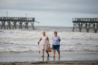 Mary McCants (left) and Amy Garrett walk near a damaged pier the morning after Hurricane Isaias came through late Monday night in North Myrtle Beach, S.C. Hurricane Isaias was downgraded to a tropical storm on Tuesday after making landfall overnight as a Category 1 hurricane.