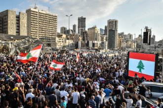 People wave Lebanese flags at a protest near the Beirut port on Tuesday. Last week's explosion has prompted new hopes for political change, but enormous challenges remain.