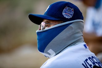 A fan wears a neck gaiter as he watches the Los Angeles Dodgers play at home against the San Francisco Giants last week.