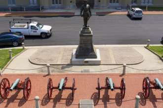 """A statue of Confederate Gen. Thomas """"Stonewall"""" Jackson stands behind cannons at the entrance to the barracks at Virginia Military Institute in Lexington, Va. Superintendent J.H. Binford Peay III resigned Monday amid allegations that the school's culture was hostile to Black cadets."""