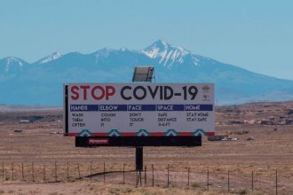 A sign warns against the Covid-19 virus near the Navajo town of Tuba City, Arizona. As the virus rages across the U.S., mitigation measures continue to be critical to save lives.