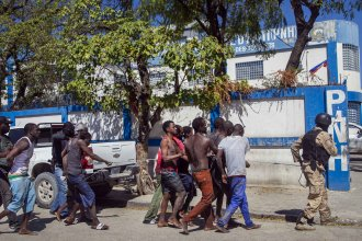 Police escort recaptured inmates back to the Croix-des-Bouquets Civil Prison after Thursday's outbreak in Port-au-Prince, Haiti. As of Friday night, authorities were still searching for more than 200 escapees.