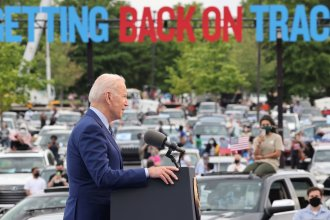 """President Joe Biden speaks during the Democratic National Committee's """"Back on Track"""" drive-in car rally in Duluth, Georgia, to celebrate his 100th day in office. Immigrant advocates were there to protest."""