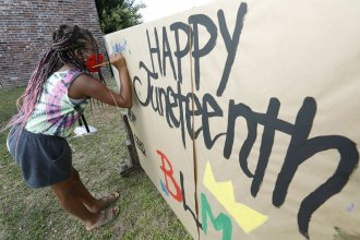 A girl paints on a poster celebrating Juneteenth in downtown Jackson, Miss., on June 19, 2020. Congress has voted to make the day a federal holiday.