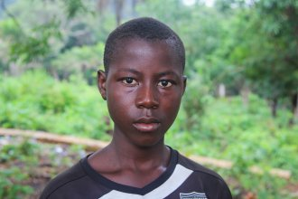 """Sahr Tarawaly, 14, works several jobs to earn money to support his mom and two siblings. """"I used to like mathematics,"""" the round-faced teenager says. """"Now I go down to the beach to fish, to have fish to eat."""""""