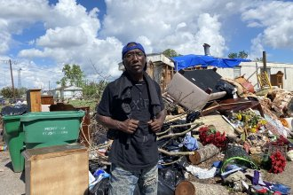 Donald Caesar, Jr., 49, stands in front of a pile of garbage. That's what's left of his family's home a month after Hurricane Ida ripped through LaPlace, La.