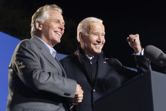President Joe Biden, right, reacts after speaking at a rally for Democratic gubernatorial candidate, former Virginia Gov. Terry McAuliffe on Tuesday, Oct. 26 in Arlington, Va. McAuliffe will face Republican Glenn Youngkin in the election on Nov. 2.