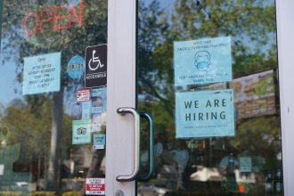 "A ""We are hiring"" sign is paired with a pandemic-themed sign in the window of a store in Miami. Restaurants and other in-person businesses are looking to hire more workers at a time when some are wary of returning to work or are busy with caregiving."