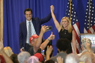 Rep. Matt Gaetz, R-Fla., and Rep. Marjorie Taylor Greene, R-Ga., raise their arms after addressing attendees of a rally Friday at The Villages in Florida.