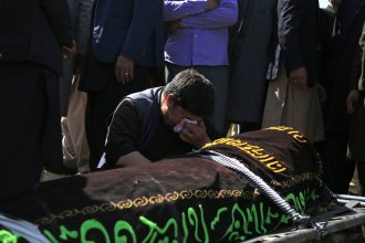 A man cries over the body of a victim of deadly bombings on Saturday near a school, at a cemetery west of Kabul on Sunday. More than 50 were killed in the attack, many of them pupils between 11 and 15 years old. More than 100 were wounded.