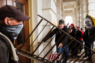 A member of a pro-Trump mob bashes an entrance of the Capitol building in an attempt to gain access on Jan. 6. The U.S. Capitol Police's inspector general has pointed to intelligence failures in the lead-up to the insurrection.