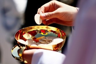 A priest holds a Holy Communion wafer in Washington, DC.