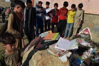 Onlookers stand next to the backpacks and books of victims of the bombing Saturday in Kabul. Most of the victims were teenage schoolgirls.