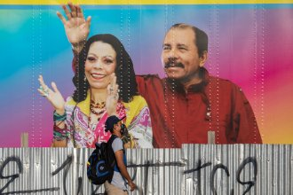 A man walks by a mobile health clinic displaying a picture of Nicaraguan President Daniel Ortega (right) and his wife and vice president, Rosario Murillo, in Managua on April 14, 2020. The government claims to be successfully combating the pandemic but health workers and critics say the toll is likely higher.