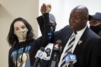 Karissa Hill, daughter of Andre Hill, raises hands with Benjamin Crump, the civil rights attorney representing Hill's family, at a news conference in February after former Columbus police officer Adam Coy was charged with murder in Hill's death.