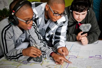 Students podcasts from the Steel City Academy in Gary, Indiana, Erin Addison (left), Evan Addison, and Andrew Arevalo (right), look over a planning map of the City of Gary.