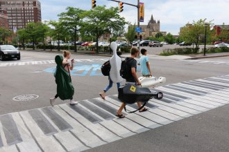 Musicians walk on a crosswalk painted like a piano Outside the Eastman School of Music in Rochester, N.Y. Increasingly, urban designers and transportation planners say this kind of art — colorful crosswalks and engaging sidewalks — leads to safer intersections, stronger neighborhoods, and better public health.