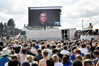 "Former NSA contractor Edward Snowden, on a video link in Moscow, speaks to the crowd on a giant screen at festival in Roskilde, Denmark, in 2016. ""You are being watched all the time and you have no privacy,"" Snowden said."