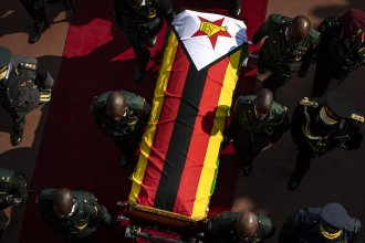 Military officers carry the casket of former president Robert Mugabe out of his state funeral at the National Sports Stadium in Harare.