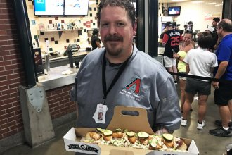 Stephen Tilder, the executive chef at Chase Field in Phoenix, holds the SI Cover Dog, a collaboration with a <em>Sports Illustrated</em> reporter.