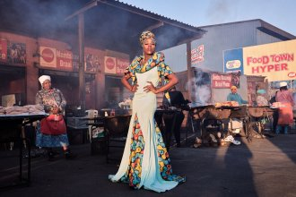 "Belinda Qaqamba Ka-Fassie poses at a community space where women cook and sell meat. She started drag as an escape from oppression she felt at Stellenbosch University for being ""black, Xhosa, poor, queer and effeminate."" ""It is through pageantry and performance that I became more inclined with my queerness and how boundless expression should be,"" she says. ""Drag became the therapist I never had."""