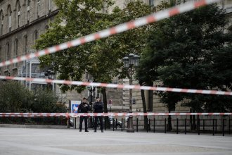 Officers stand guard outside Paris police headquarters Thursday after a man with a knife killed multiple people before he was fatally shot.