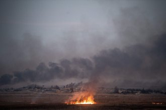 Smoke rises from the Syrian town of Tal Abyad, where a hospital was shuttered because of the fighting.