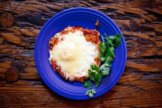 A plate of huevos rancheros topped with a basted egg.