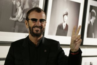 Pop icon and former Beatle Ringo Starr poses for the media in front of some of his photographs as he launches a book, <em>Photograph,</em> in London on Wednesday.