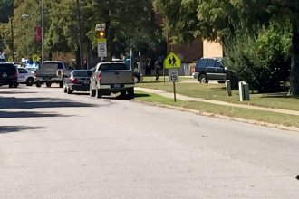 A law enforcement officer stands watch as emergency vehicles clog a road near Delta State University after an active shooter was reported in Cleveland, Miss., on Monday. One person died in the shooting and the campus remains on lockdown.
